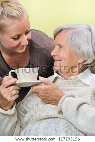 Senior woman with caregiver at home. MANY OTHER PHOTOS WITH THIS SENIOR MODEL IN MY PORTFOLIO. - stock photo