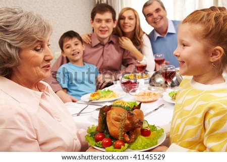 Senior woman with cooked turkey looking at her granddaughter and both smiling - stock photo