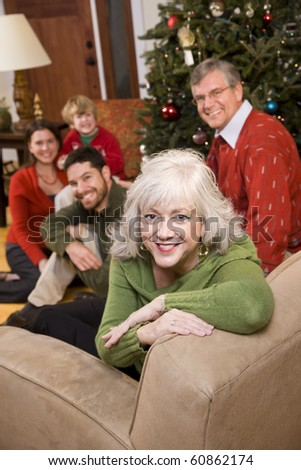 Senior woman with family by Christmas tree - three generations - stock photo