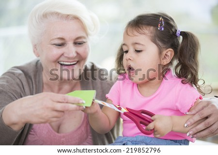 Senior woman with granddaughter cutting paper at home - stock photo