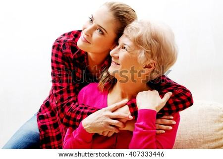 Senior woman with granddaughter or  daughter hugging on couch - stock photo