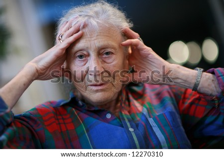 Senior woman with hands holding head. Shallow DOF. - stock photo