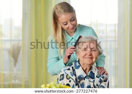 Senior woman with her caregiver in home. MANY OTHER PHOTOS FROM THIS SERIES IN MY PORTFOLIO. - stock photo