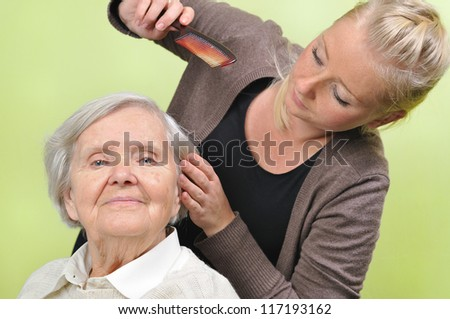 Senior woman with her caregiver in home. MANY OTHER PHOTOS WITH THIS SENIOR MODEL IN MY PORTFOLIO. - stock photo