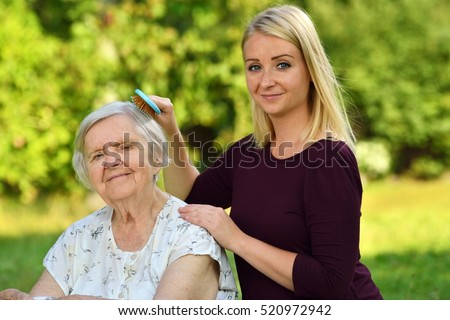 Senior woman with her caregiver in park. MANY OTHER PHOTOS WITH THIS SENIOR MODEL IN MY PORTFOLIO.