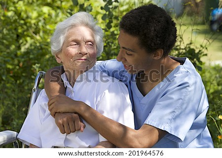 Senior woman with her very embracing and caring  caregiver outdoor - stock photo