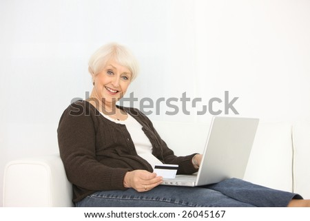 Senior woman with laptop computer and credit card