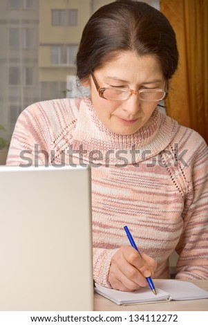 Senior woman with laptop, relaxing on the couch.