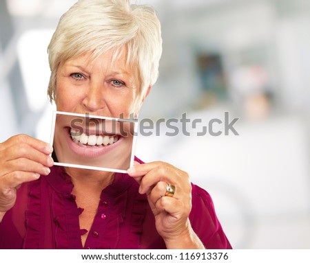 Senior Woman With Magnifying Glass Showing Teeth, Background - stock photo