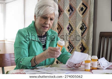 Senior woman with medication, reviewing instructions, side effects - stock photo