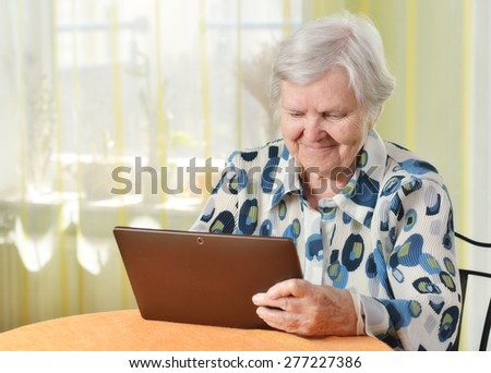 Senior woman with tablet in her room. MANY OTHER PHOTOS FROM THIS SERIES IN MY PORTFOLIO. - stock photo