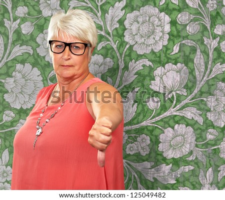 Senior Woman With Thumbs Down, Indoor - stock photo