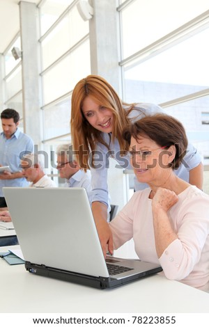 Senior woman with trainer in front of laptop computer - stock photo