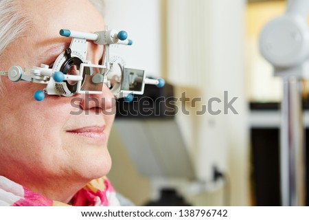 Senior woman with trial frame at optician for lens determination - stock photo