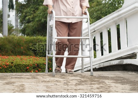 senior woman with walker in park. - stock photo