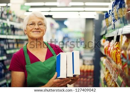 Senior woman working at supermarket - stock photo