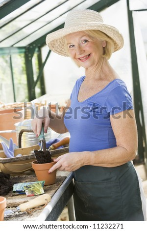 Senior woman working in greenhouse - stock photo