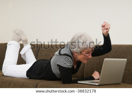 Senior woman working on a laptop, lying relaxed on the couch. - stock photo