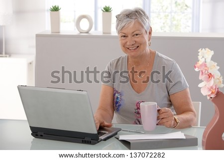 Senior woman working on laptop computer, looking at camera, drinking tea. - stock photo