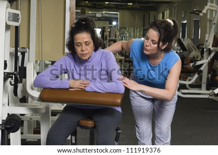 Senior woman working out in gym with her trainer - stock photo