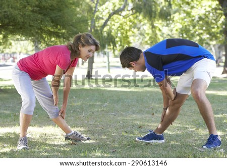 Senior Woman Working With Personal Trainer In Park - stock photo