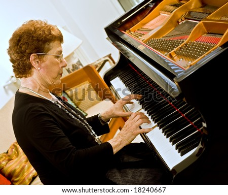 senior women pianist playing on a grand piano - stock photo