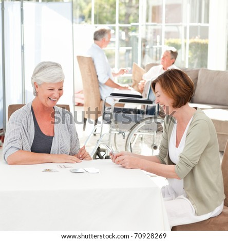 Senior women playing cards while their husbands are talking - stock photo
