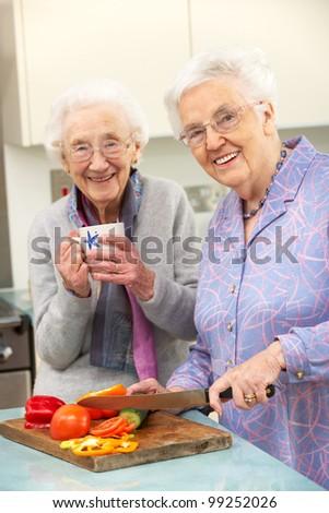 Senior women preparing meal together - stock photo