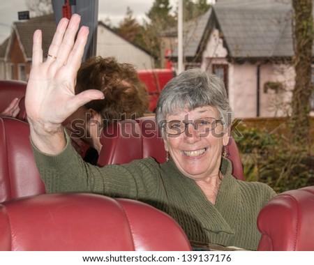 Senior women tourist on a tour bus - stock photo