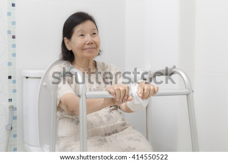 Senior women using the toilet with walker. ( focus at hand ) - stock photo