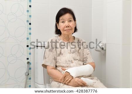 Senior women with broken arm using the toilet. - stock photo