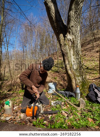 Senior woodcutter doing maintenance work for his chainsaw - stock photo