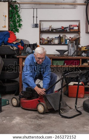 Senior worker maintaining his lawn mower in the workshop.