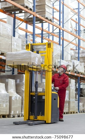 Senior worker manual forklift operator in red uniform at work in warehouse - stock photo