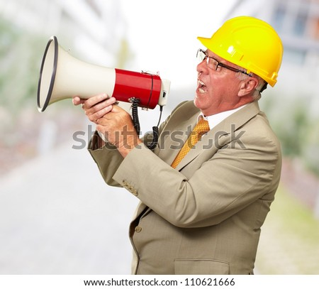 Senior Worker Shouting With Megaphone, Background - stock photo