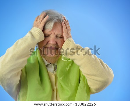 Senior worried woman with grey hairs against blue background. MANY OTHER PHOTOS FROM THIS SERIES IN MY PORTFOLIO. - stock photo