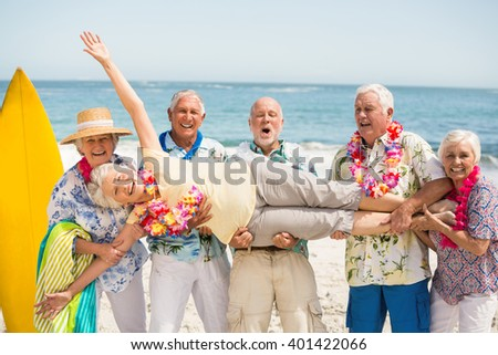 Seniors carrying senior woman on a sunny day - stock photo
