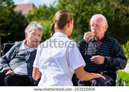 Seniors, couple of man and woman sitting in wheelchair, eating candy in garden of nursing home - stock photo