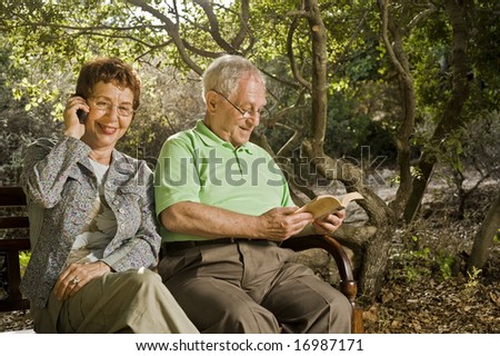 seniors couple sitting on a bench talking on the cell phone and reading in the park - stock photo