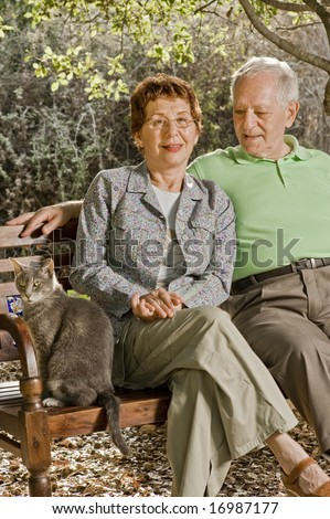 seniors couple sitting on a bench with a cat in the park - stock photo