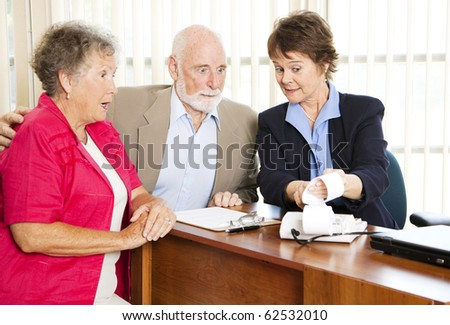Seniors get upsetting news from their financial consultant. - stock photo