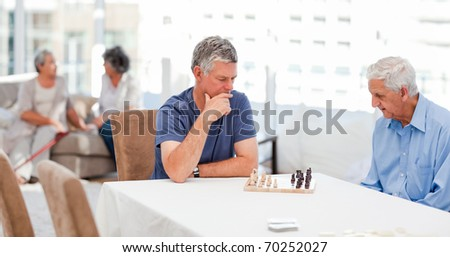Seniors playing chess at home