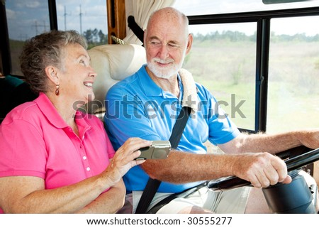 Seniors taking a trip in their motor home, using a GPS to navigate. - stock photo