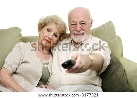 Seniors watching television together and switching channels.  White background. - stock photo
