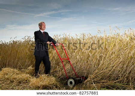 Seniot executive businessman pausing during the challenge of harvesting a field of ripe wheat with a hand lawnmower as he visualises the rewards to be gained at the completion of his task - stock photo