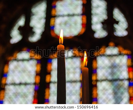 SENLIS, FRANCE - DEC 24: Two burning candles against stained  glass window in Senlis Cathedral in Christmas Eve on December 24, 2012 in Senlis, France. Senlis Cathedral was built in 12th century. - stock photo