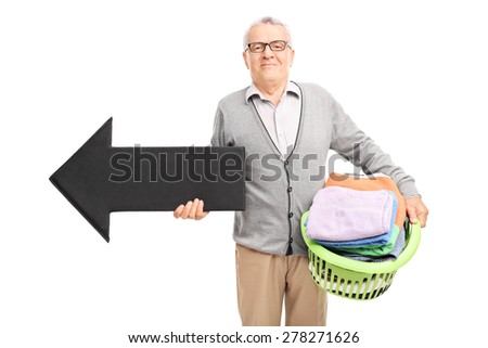 Senor gentleman holding a laundry basket full of clean clothes and a big black arrow pointing left isolated on white background - stock photo