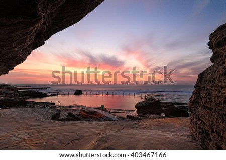 Sensational sunrise at Mahon rock pool, Maroubra, bathing the rocks and pool in vibrant reds and pink hues while a cave adds some interesting textures and framing to the scene.