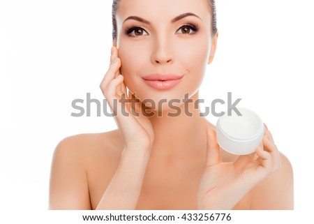 Sensitive pretty  smiling woman using cream for face - stock photo
