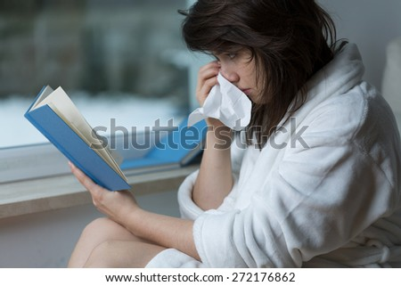 Sensitive young woman reading romance and crying - stock photo